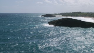 AX101_170 - 5k stock footage aerial video of a Domed rock formation in crystal blue waters along the coast, Arecibo, Puerto Rico