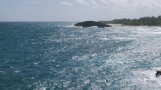AX101_171 - 5k stock footage aerial video of a Domed rock formations in crystal blue waters along the coast, Arecibo, Puerto Rico