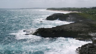 AX101_173 - 5k stock footage aerial video of Rock formations in crystal blue waters near a beach on the coast, Arecibo, Puerto Rico