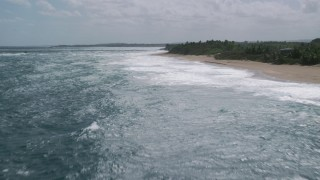 AX101_174 - 5k stock footage aerial video of Clear blue water along a beach, Arecibo, Puerto Rico