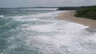 AX101_175 - 5k stock footage aerial video of Crystal blue water along a beach and tree lined coast, Arecibo, Puerto Rico