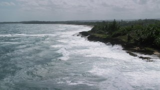 AX101_176 - 5k stock footage aerial video of Blue waters and waves against a tree lined coast, Arecibo, Puerto Rico