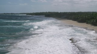 AX101_178 - 5k stock footage aerial video of Crystal blue waters along a beach and tree lined coast, Arecibo, Puerto Rico