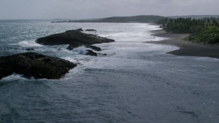 AX101_182 - 5k stock footage aerial video of Rock formation in clear waters along the coast, Barceloneta, Puerto Rico
