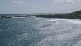 AX101_184 - 5k stock footage aerial video Flying over clear blue waters toward rock formations, Manati, Puerto Rico
