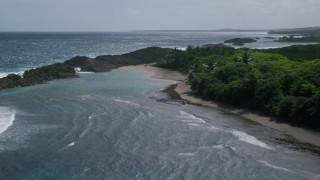 AX101_185 - 5k stock footage aerial video Flying over crystal blue waters and rock formations, Manati, Puerto Rico