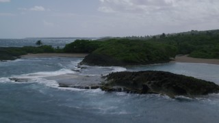AX101_187 - 5k stock footage aerial video Flying over trees, beaches and rock formations in crystal blue water, Manati, Puerto Rico