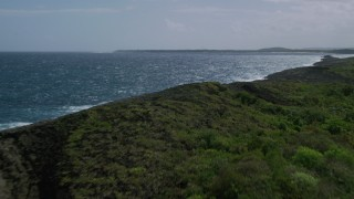 AX101_189 - 5k stock footage aerial video Flying along rocky coast and beautiful blue water, Manati, Puerto Rico