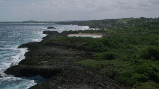 AX101_190 - 5k stock footage aerial video of Coastal tide pool bordering clear blue waters, Manati, Puerto Rico