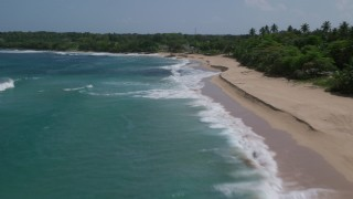 AX101_194 - 5k stock footage aerial video Alluring blue waters along a beach revealing developed land, Manati, Puerto Rico