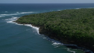 AX101_196 - 5k stock footage aerial video of Stunning blue waters along a tree lined coast, Manati, Puerto Rico