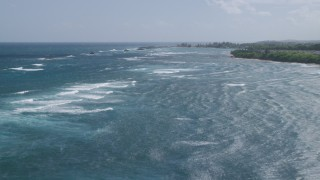 AX101_199 - 5k stock footage aerial video of Waves along the coast in clear blue water, Vega Baja, Puerto Rico