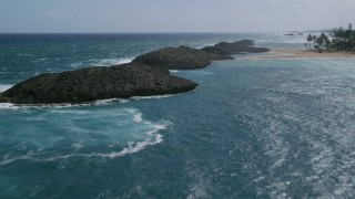 AX101_202 - 5k stock footage aerial video Flying low over rock formations in brilliant blue water and over a beach, Vega Baja, Puerto Rico