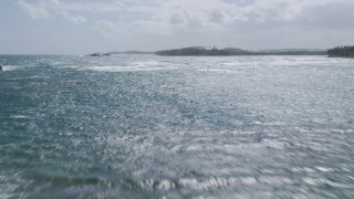 AX101_203 - 5k stock footage aerial video Flying low over waves in sparkling blue water, Vega Baja, Puerto Rico