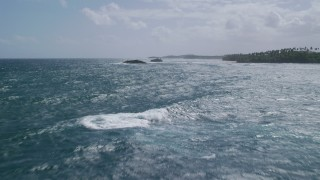AX101_204 - 5k stock footage aerial video Flying low along sparkling waters toward rock formations along the coast, Vega Baja, Puerto Rico
