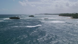 AX101_205 - 5k stock footage aerial video Flying low among rock formations over pristine blue waters, Vega Baja, Puerto Rico Day Partly Cloudy Approach Low Altitude