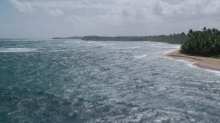 AX101_206 - 5k stock footage aerial video Flying low over waves in blue waters along the coast, Vega Baja, Puerto Rico