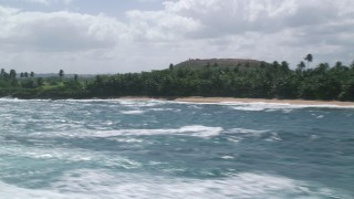 AX101_207 - 5k stock footage aerial video Flying along the coast with lush vegetation, Vega Baja, Puerto Rico