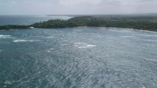 AX101_209 - 5k stock footage aerial video Flying over blue waters toward tree covered coast, Vega Alta, Puerto Rico