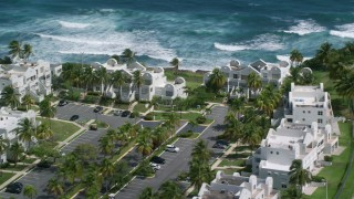 AX101_219 - 5k stock footage aerial video of Condominiums situated on the coast of pristine blue waters, Dorado, Puerto Rico