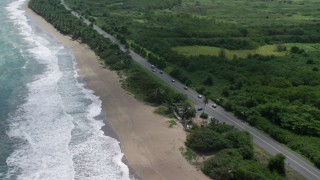 AX101_223 - 5k stock footage aerial video tilting down on roadside shop along coastal highway, Dorado, Puerto Rico
