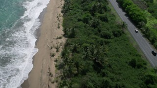 AX101_224 - 5k stock footage aerial video of a Beach and highway along the coast and blue waters, Dorado, Puerto Rico