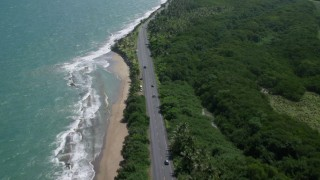 AX101_226 - 5k stock footage aerial video of a Highway along the coast of crystal blue waters, Dorado, Puerto Rico