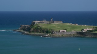AX101_236 - 5k stock footage aerial video of the Back of Fort San Felipe del Morro in crystal blue waters, Old San Juan Puerto Rico