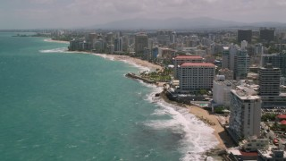 AX102_003 - 5k stock footage aerial video of Hotels and high-rises along the coast and crystal blue waters, San Juan, Puerto Rico