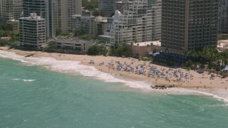 AX102_004 - 5k stock footage aerial video of Tourists on a beach enjoying clear blue waters, San Juan, Puerto Rico