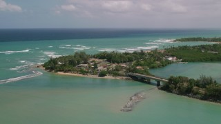 AX102_015 - 5k stock footage aerial video of Coastal shops and beach along crystal turquoise waters, Loiza, Puerto Rico