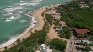 AX102_016 - 5k stock footage aerial video of Clear turquoise waters and shops along the beach, Loiza, Puerto Rico