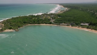 AX102_017 - 5k stock footage aerial video of Coastal homes and turquoise waters along highway, Loiza, Puerto Rico