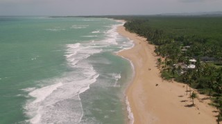AX102_020 - 5k stock footage aerial video of Tree lined beach along turquoise water, Loiza, Puerto Rico