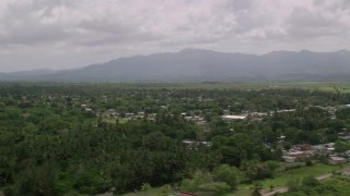 AX102_031 - 5k stock footage aerial video of Rural neighborhoods nestled in trees near a mountain, Loiza, Puerto Rico