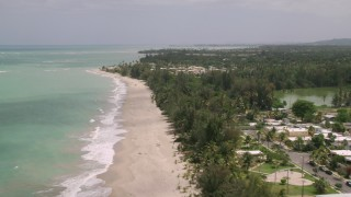 AX102_033 - 5k stock footage aerial video of Condominiums and beachfront homes along clear turquoise waters, Loiza, Puerto Rico