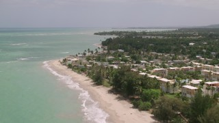 AX102_034 - 5k stock footage aerial video Flying by beachfront homes along beach and turquoise waters, Loiza, Puerto Rico