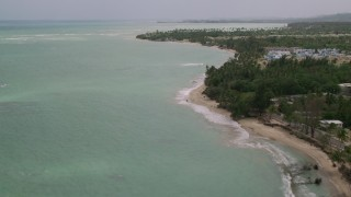 AX102_035 - 5k stock footage aerial video Flying along a tree lined beach and crystal turquoise waters, Loiza, Puerto Rico