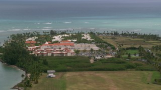 AX102_042 - Aerial stock footage of Golf resort resting along clear turquoise waters, Gran Melia Golf Resort, Puerto Rico