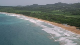 AX102_052 - 5k stock footage aerial video of Crystal blue waters along beach and jungle, Luquillo, Puerto Rico
