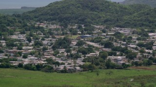 AX102_055 - 5k stock footage aerial video of Homes among tree covered hills, Fajardo, Puerto Rico