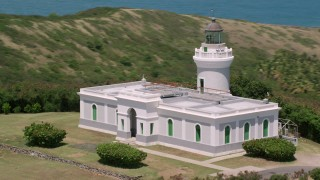 AX102_065 - 5k stock footage aerial video of Cape San Juan Light above clear blue waters, Puerto Rico