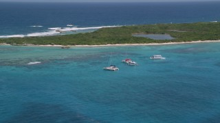 AX102_074 - 5k stock footage aerial video of Catamarans in tropical blue waters with reefs near an island, Rada Fajardo, Puerto Rico
