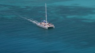 AX102_076 - 5k stock footage aerial video Tracking a catamaran in crystal clear blue tropical waters, Rada Fajardo, Puerto Rico