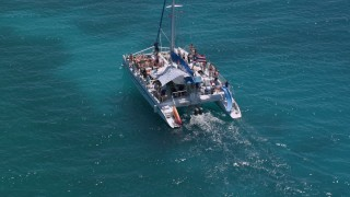AX102_077 - 5k stock footage aerial video Flying away from a catamaran in tropical blue water, Rada Fajardo, Puerto Rico