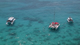 AX102_078 - 5k stock footage aerial video Flying away from catamarans in tropical blue waters, Rada Fajardo, Puerto Rico