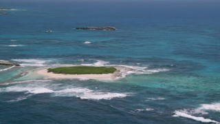 AX102_086 - 5k stock footage aerial video of Tiny green island in tropical blue waters, Puerto Rico