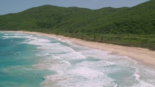 AX102_117 - 5k stock footage aerial video of Turquoise blue waters along a Caribbean beach and lush vegetative coast, Culebra, Puerto Rico