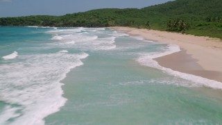 AX102_124 - 5k stock footage aerial video of Waves in turquoise waters along a small Caribbean  beach, Culebra, Puerto Rico
