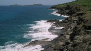AX102_128 - 5k stock footage aerial video of Sapphire blue waters against a rugged coast, Culebra, Puerto Rico